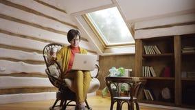 Mujer hermosa con café de consumición del ordenador portátil en ático almacen de video