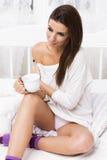 Mujer hermosa con café en la cama Imagen de archivo