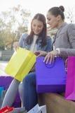 Mujer hermosa con el amigo que mira en el panier al aire libre Imagenes de archivo