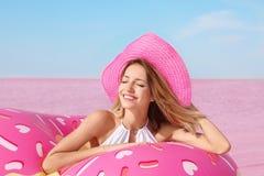 Mujer hermosa con el anillo inflable cerca del lago imagen de archivo
