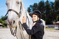 Mujer hermosa con el arte rojo del clavo encariñado con equestrianism foto de archivo
