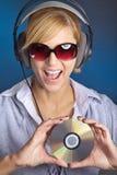 Mujer hermosa con el auricular y el Cd Foto de archivo