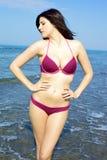 Mujer hermosa con el bikiní rosado que presenta en el mar Imagen de archivo