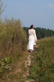 Mujer hermosa con el busket en el campo del verano Foto de archivo