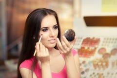 Mujer hermosa con el cepillo del maquillaje que mira en un espejo imagenes de archivo