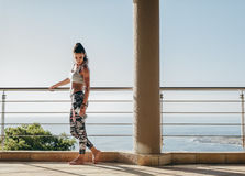 Mujer hermosa con el cuerpo muscular que se coloca en el balcón Fotos de archivo libres de regalías