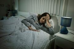 Mujer hermosa con el dolor de cabeza fuerte que miente en la cama que tiene fiebre Foto de archivo