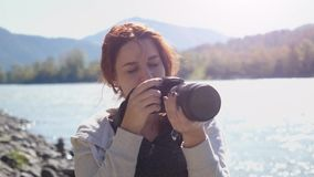 Mujer hermosa con el fotógrafo rojo del pelo que toma la foto usando cámara profesional al aire libre en alza El tomar femenino d almacen de video