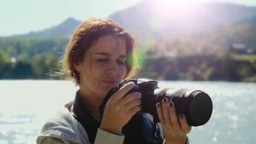 Mujer hermosa con el fotógrafo rojo del pelo que toma la foto usando cámara profesional al aire libre en alza El tomar femenino d metrajes