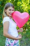 Mujer hermosa con el globo en forma de corazón imagen de archivo libre de regalías