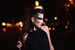 Mujer hermosa con el maquillaje de Halloween que presenta en la calle Mirada modelo a un lado Cierre para arriba Fondo de la ciud fotos de archivo libres de regalías