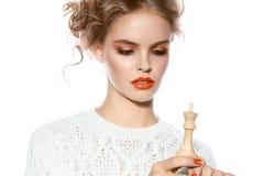Mujer hermosa con el maquillaje de la tarde que lleva a cabo un pedazo de ajedrez del rey Imagen de archivo libre de regalías