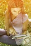Mujer hermosa con el ordenador de la tablilla en parque Fotografía de archivo