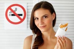 Mujer hermosa con el paquete de cigarrillos y de la muestra de no fumadores Fotografía de archivo libre de regalías