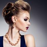 Mujer hermosa con el peinado del estilo y joyería del oro con el bergantín Imagen de archivo