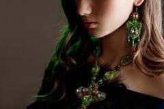 Mujer hermosa con el pelo hermoso, maquillaje y con el collar de lujo en fondo verde oscuro fotografía de archivo libre de regalías