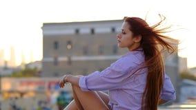 Mujer hermosa con el pelo largo que se sienta en un tejado Concepto de la soledad
