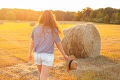 Mujer hermosa con el pelo rizado largo en campo de rastrojo del verano Imagen de archivo libre de regalías