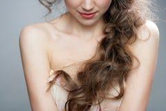 Mujer hermosa con el pelo rizado largo sano Foto de archivo libre de regalías