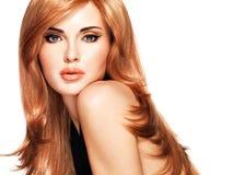 Mujer hermosa con el pelo rojo de largo recto en un vestido negro. Imágenes de archivo libres de regalías