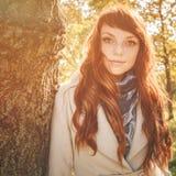 Mujer hermosa con el pelo rojo en parque del otoño Fotografía de archivo