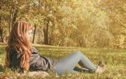 Mujer hermosa con el pelo rojo en parque del otoño Fotos de archivo libres de regalías