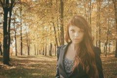 Mujer hermosa con el pelo rojo en parque del otoño Fotos de archivo