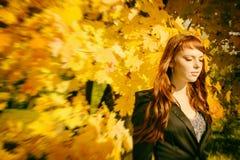 Mujer hermosa con el pelo rojo en parque del otoño Foto de archivo