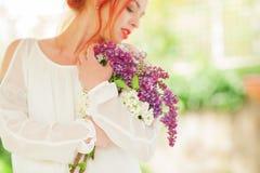 Mujer hermosa con el pelo rojo que lleva a cabo la floración blanca y violeta en sus manos, jardín al aire libre de la lila Foto de archivo libre de regalías