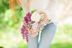 Mujer hermosa con el pelo rojo que lleva a cabo la floración blanca y violeta en sus manos, jardín al aire libre de la lila Imagen de archivo libre de regalías