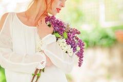 Mujer hermosa con el pelo rojo que lleva a cabo la floración blanca y violeta en sus manos, jardín al aire libre de la lila Foto de archivo