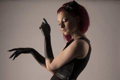 Mujer hermosa con el pelo rojo y la pintura negra en las manos Imagen de archivo libre de regalías