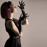 Mujer hermosa con el pelo rojo y la pintura negra en las manos Fotografía de archivo