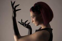Mujer hermosa con el pelo rojo y la pintura negra en las manos Fotografía de archivo libre de regalías