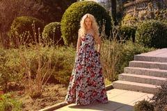 Mujer hermosa con el pelo rubio en vestido elegante en el parque Imagen de archivo libre de regalías