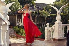 Mujer hermosa con el pelo rubio en vestido rojo lujoso imagen de archivo libre de regalías