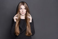 Mujer hermosa con el pelo rubio oscuro largo, magnífico La visten en vestido caliente del punto del gris con una capilla Fotos de archivo