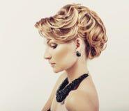 Mujer hermosa con el pelo rubio que lleva el vestido poco negro que toca su opinión del cuello de la parte posterior en blanco Fotos de archivo libres de regalías