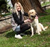 Mujer hermosa con el perro en el parque Imagen de archivo