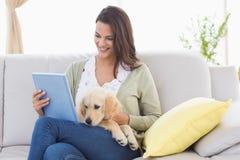 Mujer hermosa con el perro usando la tableta digital en el sofá Fotografía de archivo