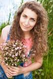 Mujer hermosa con el ramo de sonrisa rosada de las flores Foto de archivo