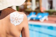 Mujer hermosa con el sol exhausto por la crema del sol en su hombro por la piscina Factor de protecci?n de Sun en las vacaciones, imagen de archivo