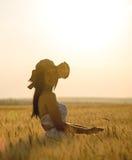 Mujer hermosa con el sombrero del verano en campo de trigo en la puesta del sol Fotografía de archivo libre de regalías