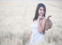Mujer hermosa con el sombrero del verano en campo de trigo en la puesta del sol Foto de archivo