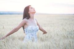 Mujer hermosa con el sombrero del verano en campo de trigo en la puesta del sol Fotos de archivo libres de regalías