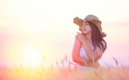 Mujer hermosa con el sombrero del verano en campo de trigo en la puesta del sol Fotografía de archivo