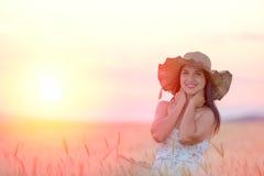 Mujer hermosa con el sombrero del verano en campo de trigo en la puesta del sol Imagen de archivo libre de regalías