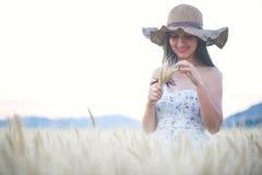 Mujer hermosa con el sombrero del verano en campo de trigo en la puesta del sol Imagenes de archivo