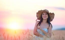 Mujer hermosa con el sombrero del verano en campo de trigo en la puesta del sol Fotos de archivo