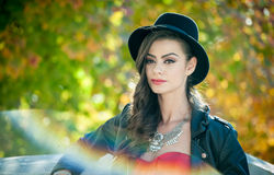 Mujer hermosa con el sombrero negro que presenta en parque otoñal Tiempo de gasto moreno joven durante otoño en bosque foto de archivo